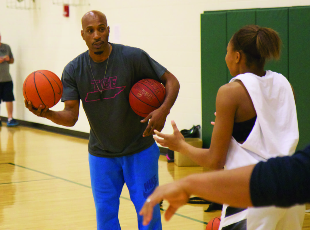 David Crockett instructional assist and former assistant basketball coach Damon Johnson helps a youth basketball player during one of his team's practices.