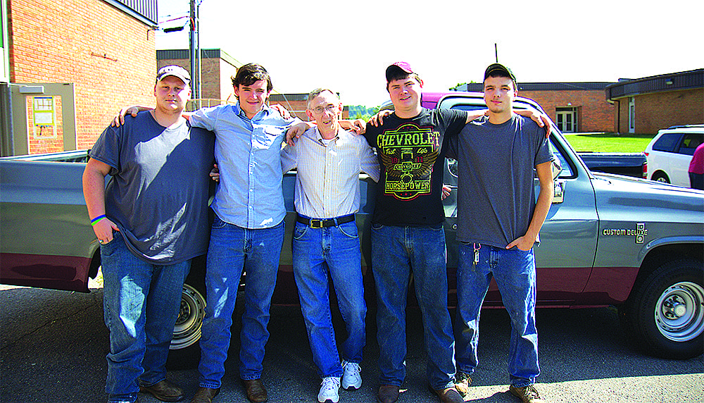 David Crockett students Billy Baker, Jonathan Phillips, David Seaboch and Dustyn Hull pose with Douglast Gourley (center) after they presented him his truck.