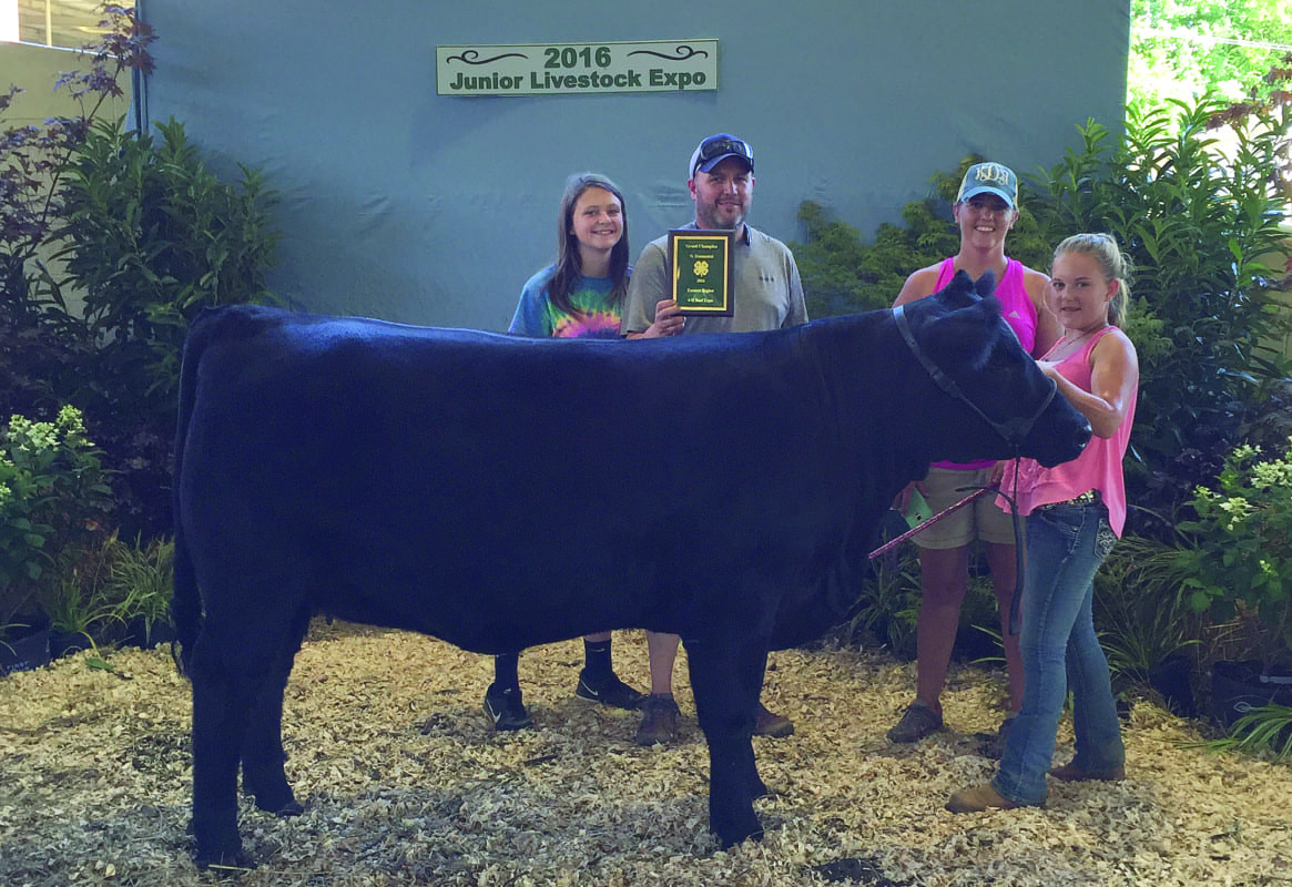 Makayla Dockery, right, holds onto her champion heifer. She is joined by her mother, Kristina; father, Jeremy; and sister, Abby Dockery, after she was awarded her Grand Champion plaque.