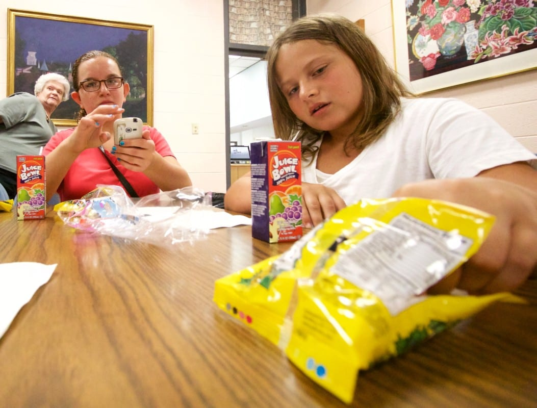 Emily Marino, left, and Kaitlin Marino, enjoy a snack at the library.