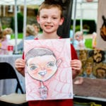 Aaron Halliburton, age 8, shows off artwork.