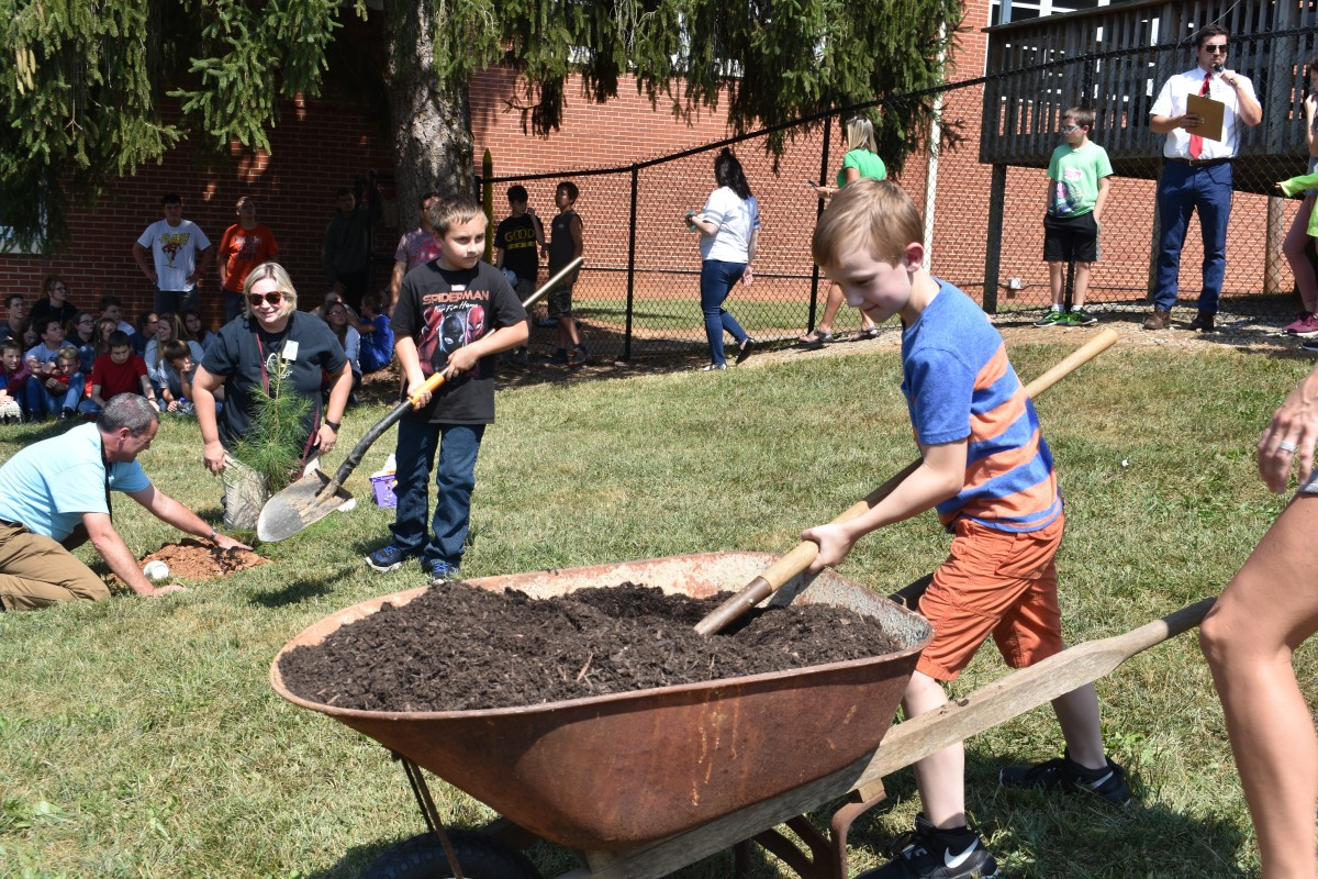 Logan Stevenson, fourth grade, takes advantage of a handy shovel and wheel barrow to help with the planting.