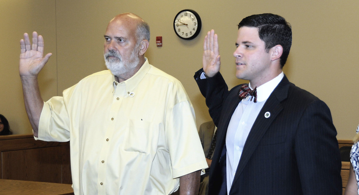 Washington County 8th District Commissioners Steve Light, left, and Matthew Morris, right, swear in during a ceremony in 2014. The Washington County Commission will temporarily fill Morris' seat while he is on military deployment.