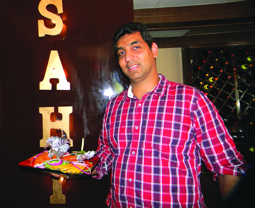 Sahib's owner, Vivek Vatrana, shows off one of the restaurant's  speciality dishes, chicken masala, also pictured above.